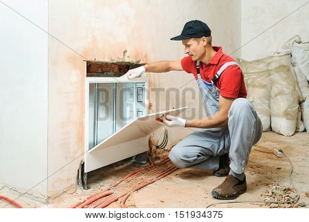 Installation of home heating. Worker installs metal box for distribution of water in the heating system.