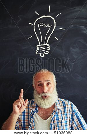 Excited aged man in stylish clothes is showing the concept of having an idea with chalk light bulb drawn on blackboard behind him