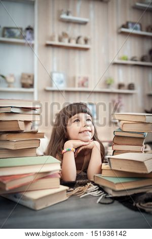 Little Cheerful Girl With Stack Of Books In Library;