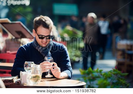 Man checking his cellphone while sitting at outdoors street cafe.