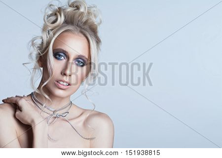 Portrait of a beautiful young blonde woman. Girl with fashion hairstyle and makeup. Trendy grey leather choker. Copyspace