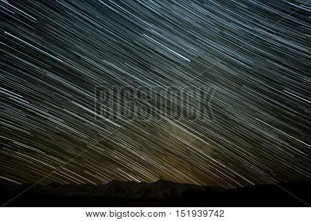 Beautiful night view of the starry sky with traces of stars in the form of tracks on the background of the contours of mountains and snowy peaks