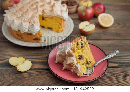 Apple cake with lemon curd and meringue on wooden background.