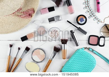Flat lay of women cosmetics and accessories on white wooden background