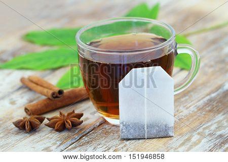 Tea bag leaning against cup of tea, anise and cinnamon