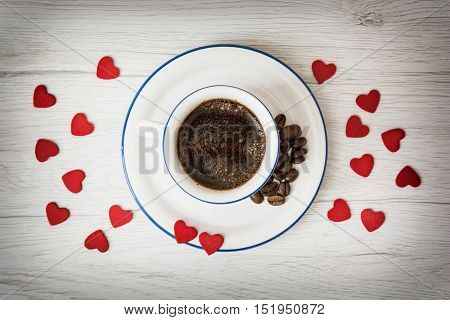 Ceramic cup of coffee with little red hearts on the wooden background. Coffee beans. Stylish still life. Refreshment theme. Valentine's Day. Love theme.