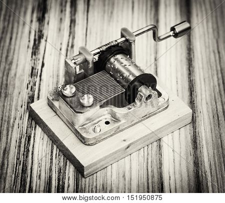 Old little music box on the wooden background. Retro style. Musical instrument. Black and white photo.