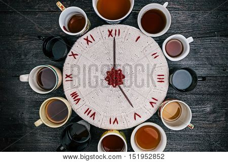 Knitted white and red clock with needle arrows reading five in the middle of the circle of various tea cups and mugs. Flat lay