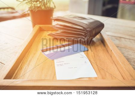 Receipt and credit card with wallet on wooden tray vintage tone.