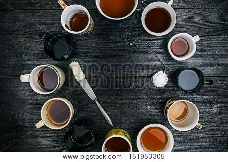 Pocket watch reading five and butter knife in the middle of the circle of various tea cups and mugs. Flat lay