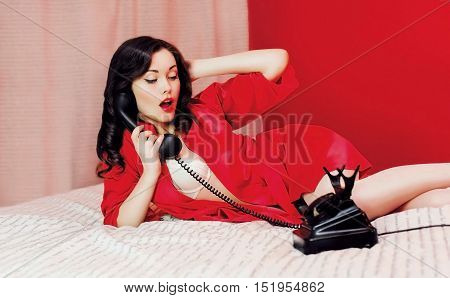 Beautiful Sexy Brunette Woman Lying On Bed Talking On The Retro Vintage Telephone. Pin-up Style
