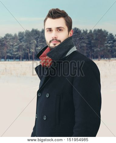 Fashion portrait handsome elegant bearded man wearing a black coat in winter day over snowy forest