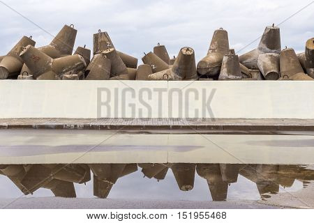 Massive stack of breakwater in cloudy day with reflection in rain puddle