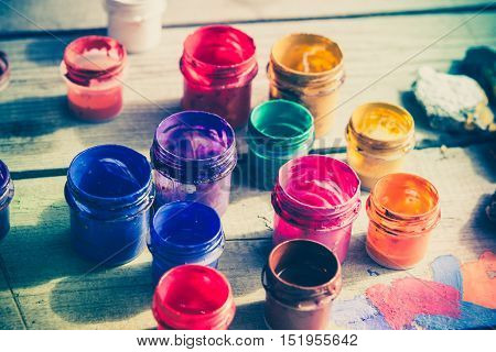many small paint jars with different colors on a wooden surface open jars and lids are close. Creative virtuosity artistry