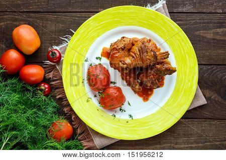Chicken legs with tomato sauce and marinated tomatoes without skins in their own juice. The top view.