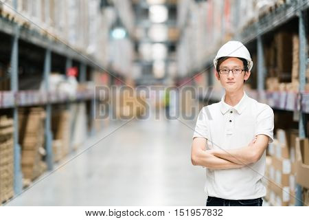 Handsome young Asian engineer or technician or worker warehouse or factory blur background industry or logistic concept with copy space