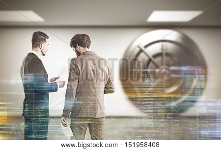 Two bank employees are standing in lobby near giant round vault door. Cityscape is at the foreground. Concept of banking. Double exposure. 3d rendering