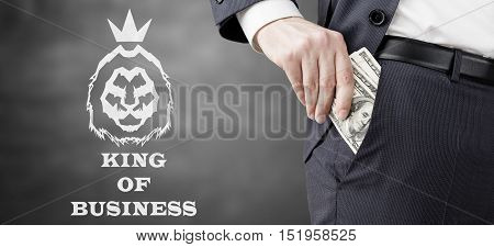 Close up of businessman putting several dollar bills into his pocket. King of business sketch is depicted beside him. Concept of money laundering