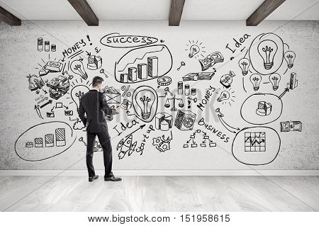 Rear view of businessman with smartphone standing near concrete wall with startup icons.