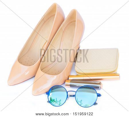 Nude colored high heels still life with wallet, sun glasses and lipstick isolated on white background