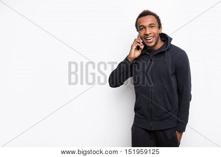 Positive African American guy talking on his phone while wearing hoodie and standing against white background. Mock up
