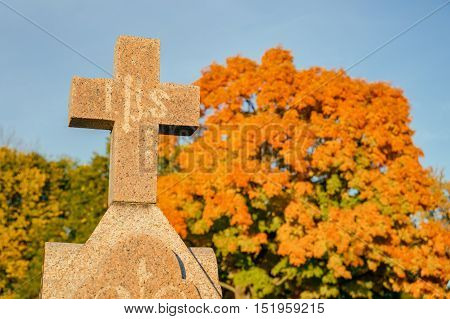 Cross in a cemetery with large maple tree in the background in Autumn (Beloeil Quebec Canada)