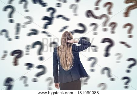Woman scratching her head and standing in a room full of floating blurred question marks. Concept of questions and answers. Toned image
