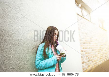 Cute young girl in pink sweater holding a cup with a straw. Sunny day. Funny mood.