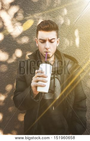 Cute young boy in jacket drinkers drink. Sunny day. Funny mood.