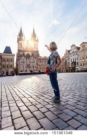 Beautiful young woman points to the Church of Virgin Mary in Old Town Square in Prague. Kostel Panny Marie pred Tynem.
