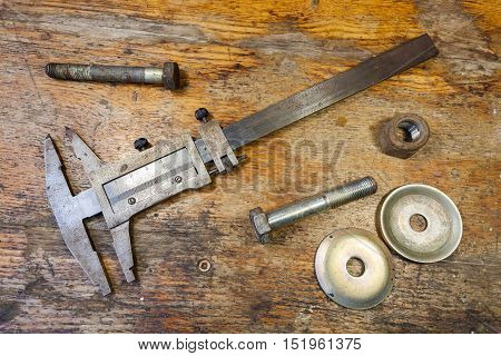 Caliper bolt and nut on a table in a workshop