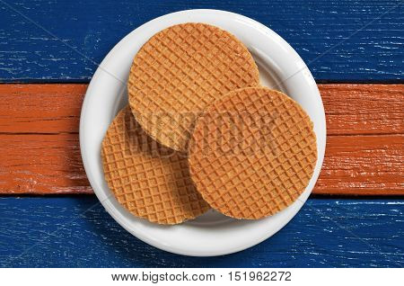 Round waffles with caramel Round waffles with caramel in plate on colorful wooden table top view