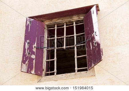 The wall of the old prison open window with bars on the escape of criminals