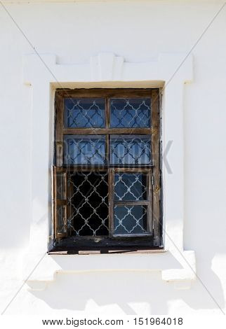 Old white wall of castle prison with a window with bars from escaping