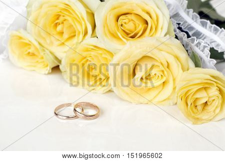 Bouquet of yellow roses and wedding rings on a white background