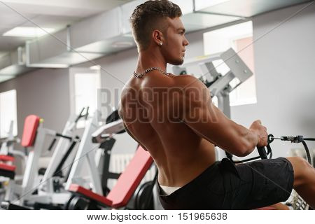 Back view of muscular young man trains on simulator