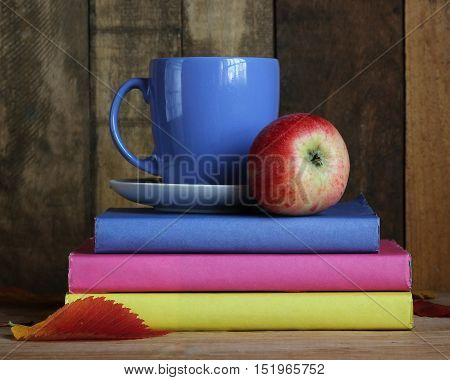 Textbooks cup apple and autumn leaves. Back to school. Still life with books.