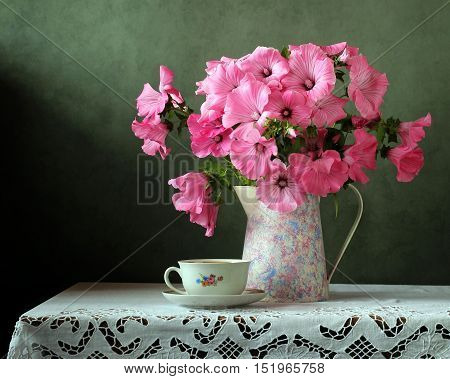Still-life with a bouquet in the retro jug and cup on the table with a white lace tablecloth.