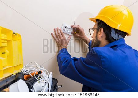 electrician wearing uniform and helmet installing wall socket