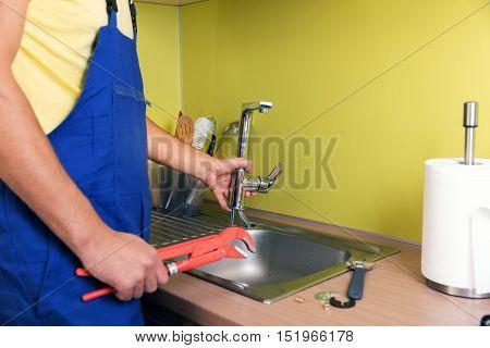 plumber working in domestic kitchen repairing faucet