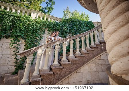 young couple in love standing on stone stairs with a handrail.