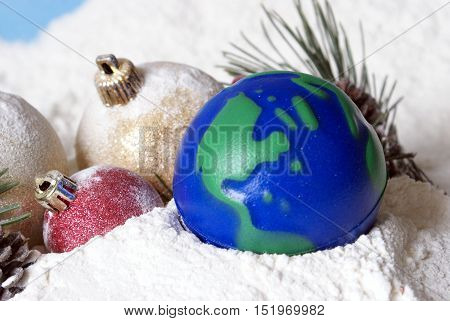A bright and cheerful Christmas scene full of snowy baubles and pines with an Earths globe.