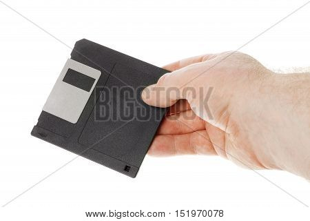 One human hand holding a black 3.5 inch magnetic floppy disk isolated on white background.
