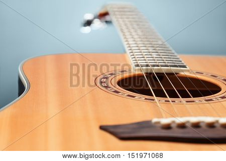 Close-up of guitar lying on cold pale-blue background. Low aperture shot selective focus
