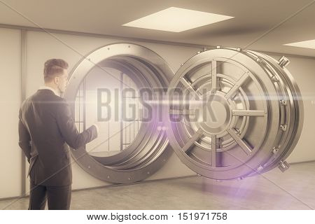 Rear view of man standing with smartphone near brown bank vault. Concept of money storage. Toned image