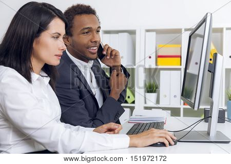 African American guy is on his smartphone. He is looking at his colleague's computer screen. Concept of multitasking