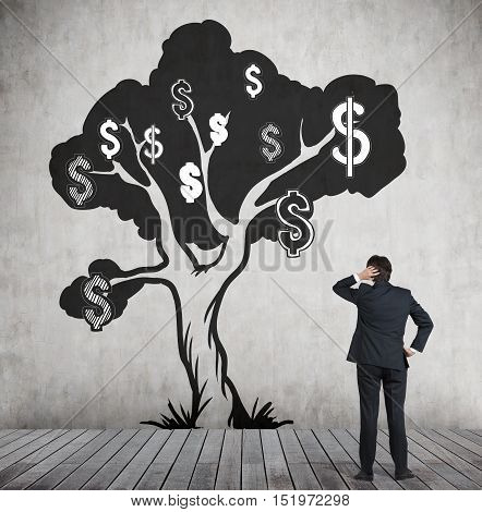 Rear view of man scratching his head and looking at concrete wall with dollar tree sketch drawn on it. Dollar signs are black and white. Concept of earning.