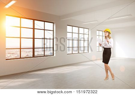 Woman in business suit and hardhat is standing in empty room with concrete wall and windows. 3d rendering. Mock up. Toned image