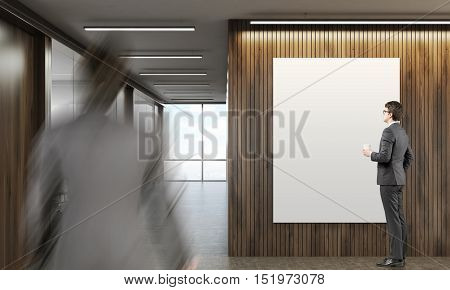 Two people in company's lobby. One is looking at poster on wooden wall. The second is approaching him. Mock up. 3d rendering