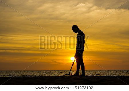 a treasure hunter with Metal detector on sunset on the beach
